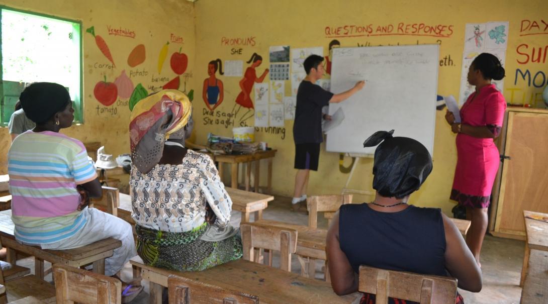 Pasante ayuda a emprendedores en Ghana discutiendo planes de negocios.